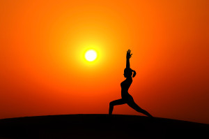 Silhouette of woman doing yoga meditation during sunset with nat